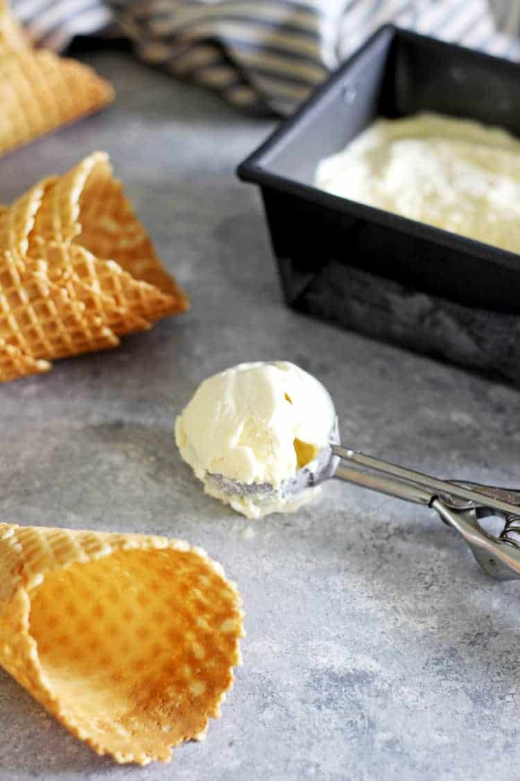 Scoop of no churn vanilla ice-cream with container of ice-cream and waffle cones