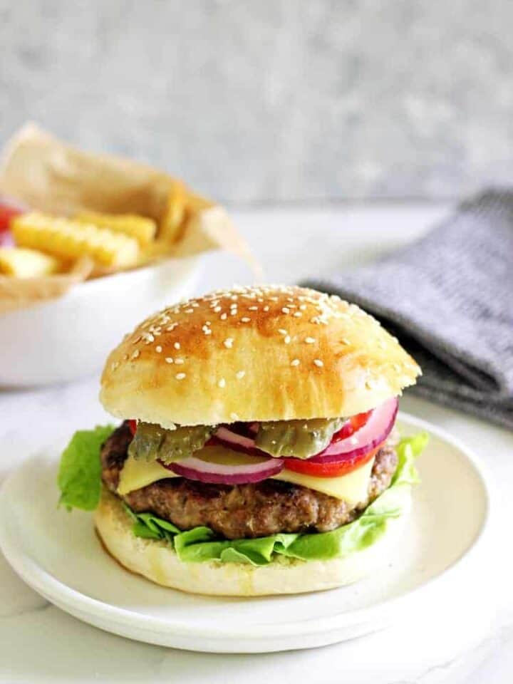 Homemade beef burger with fries in the background