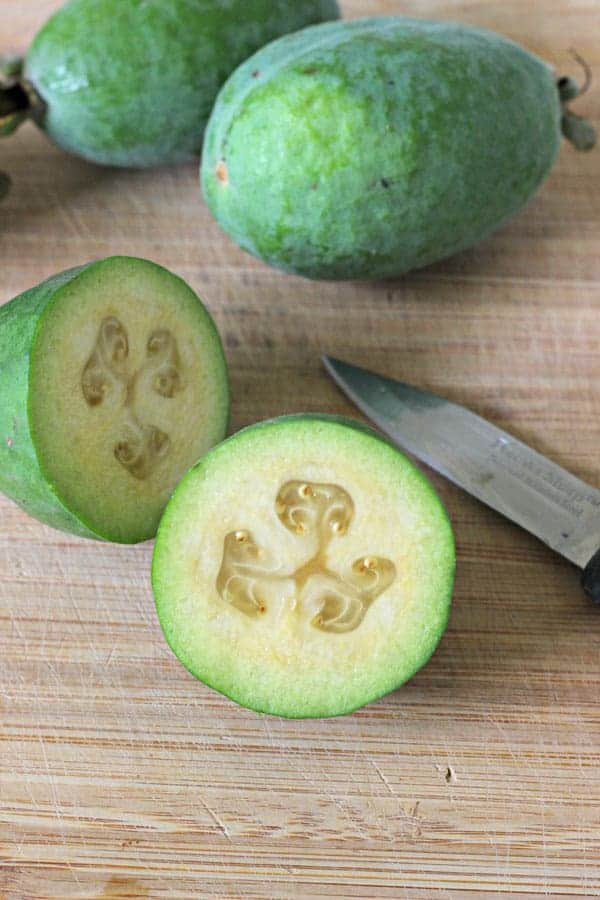 Feijoa on chopping board cut in half with knife