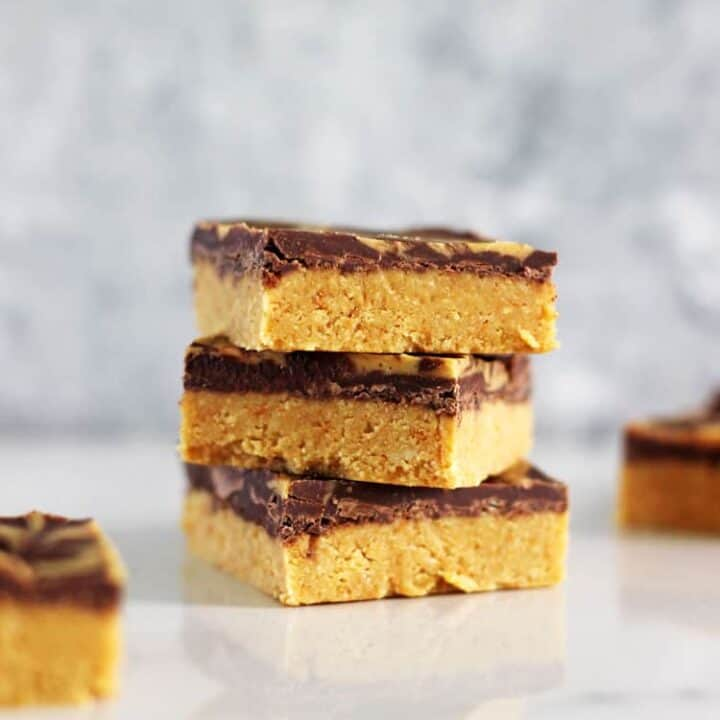 3 pieces of peanut butter bars stacked on a white background