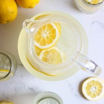 Pitcher of homemade lemonade on a white background with jars of lemonade