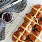 Tray of hot cross buns with jar of jam and tea towel