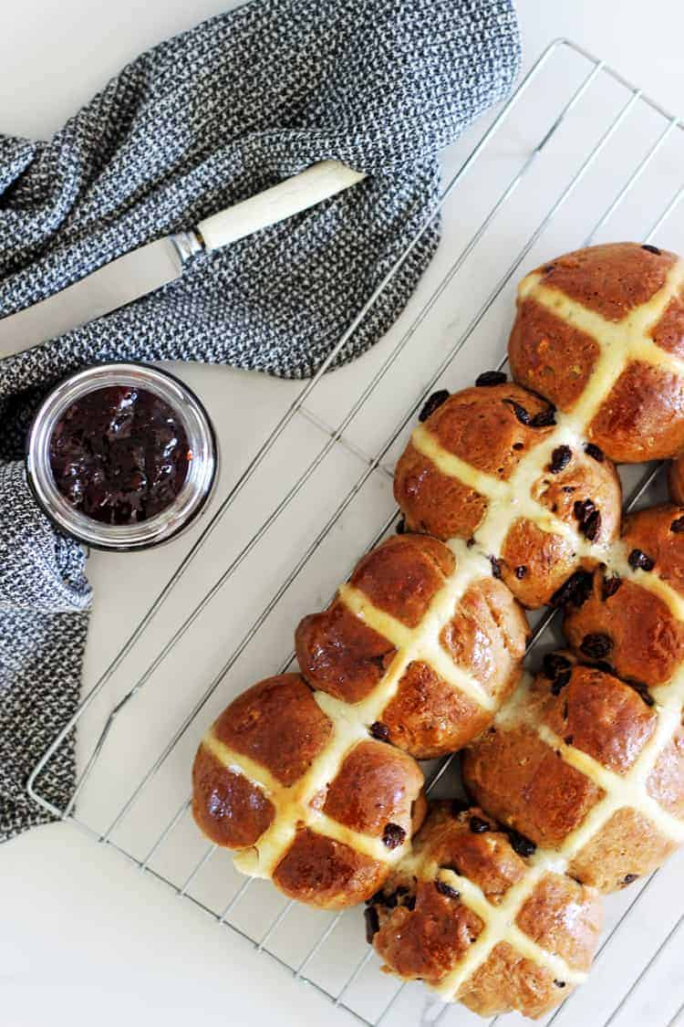Tray of hot cross buns with jar of jam and tea towel