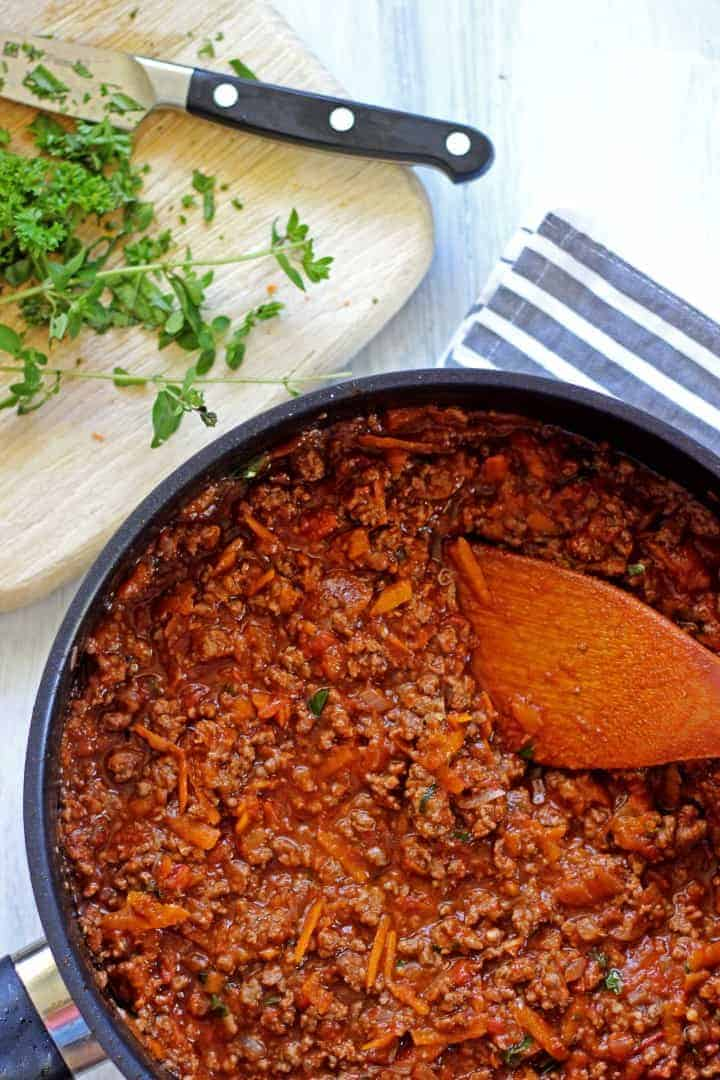 Frying pan with bolognese sauce and fresh herbs