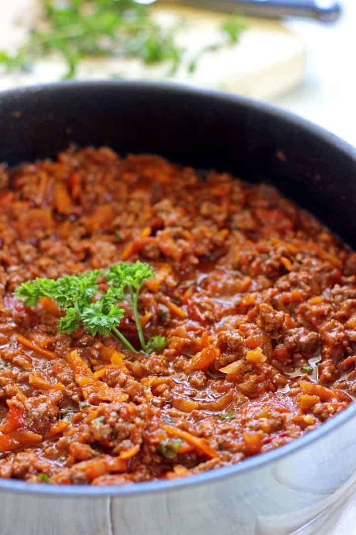 Frying pan with beef bolognese and fresh parsley