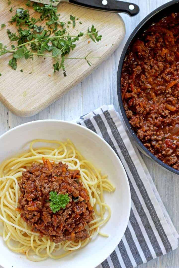 Bowl of spaghetti bolognese with fresh herbs and pan of bolognese