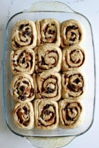 Hot Cross Bun Cinnamon Rolls! The perfect combination of delicious cinnamon rolls with all the spices and dried fruit that you love about hot cross buns! A must have for Easter brunch | thekiwicountrygirl.com