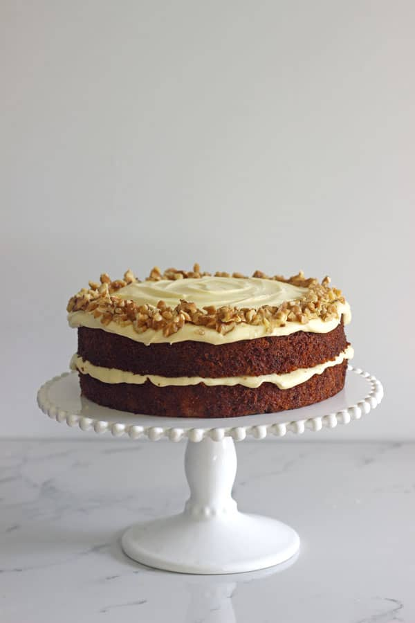 Double layer carrot cake with cream cheese frosting on a white cake stand on white marble background