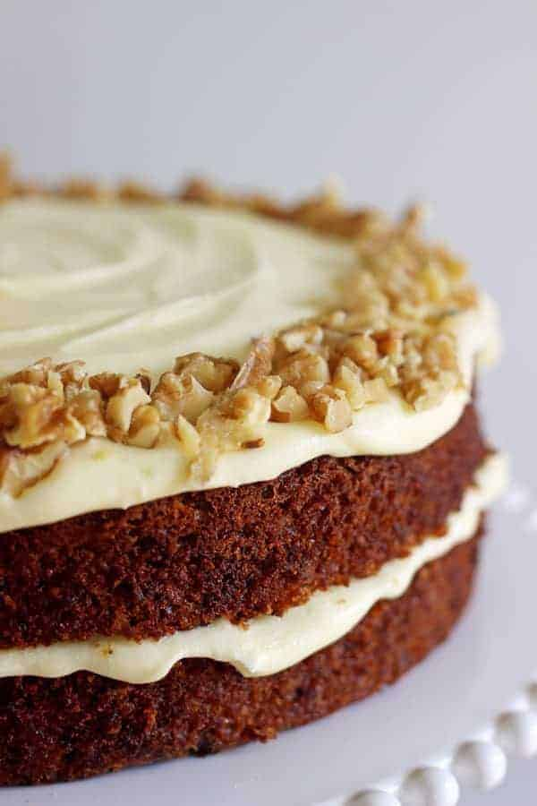 CLose up of double layer carrot cake with cream cheese frosting on a white cake stand on white marble background