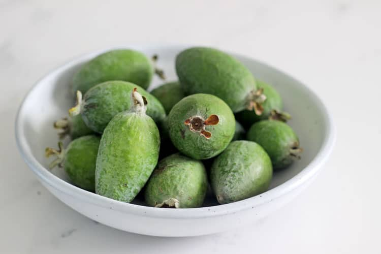 White speckled bowl of feijoas on a white marble background
