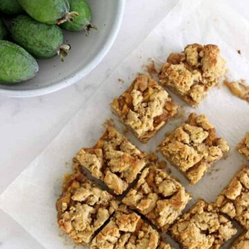 Feijoa crumble slice cut into pieces on a white marble background