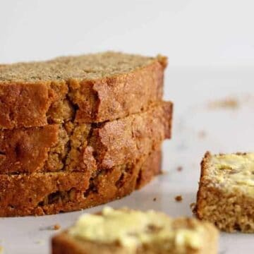 Three slices of zucchini bread in a stack on a white background with a buttered piece of zucchini bread in front