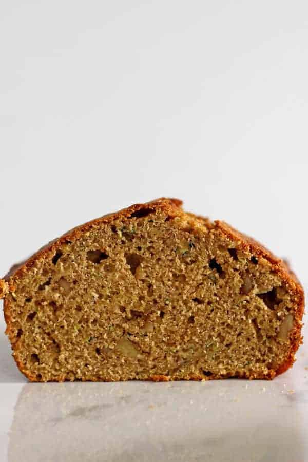 Half loaf of zucchini bread on white background