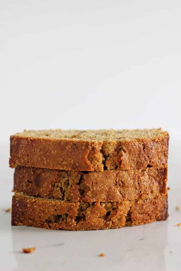 Three slices of zucchini bread in a stack on a white background