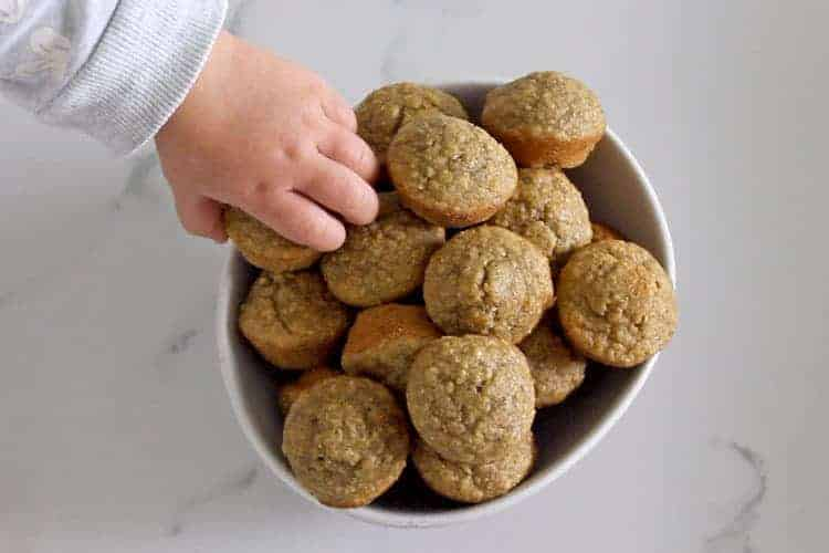 Bowl of mini banana oatmeal muffins with baby hand reaching one