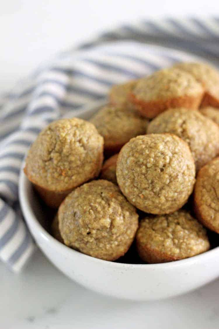 Bowl of mini banana oatmeal muffins with blue striped tea towel