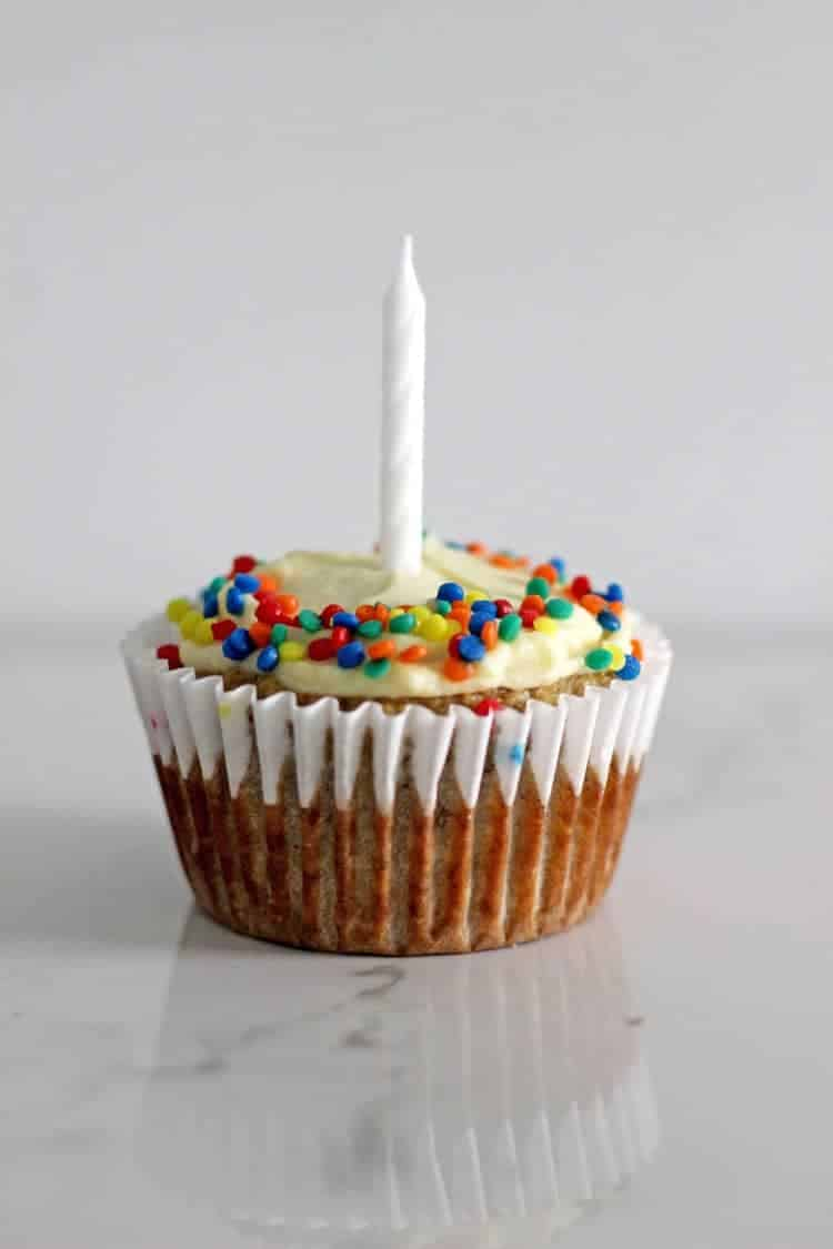 Banana muffin with cream cheese frosting and sprinkles with 1 candle on a white background
