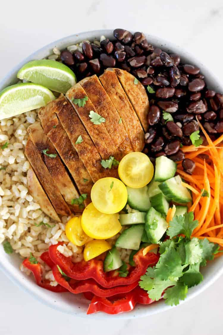 Chicken, rice, black beans and salad in a bowl