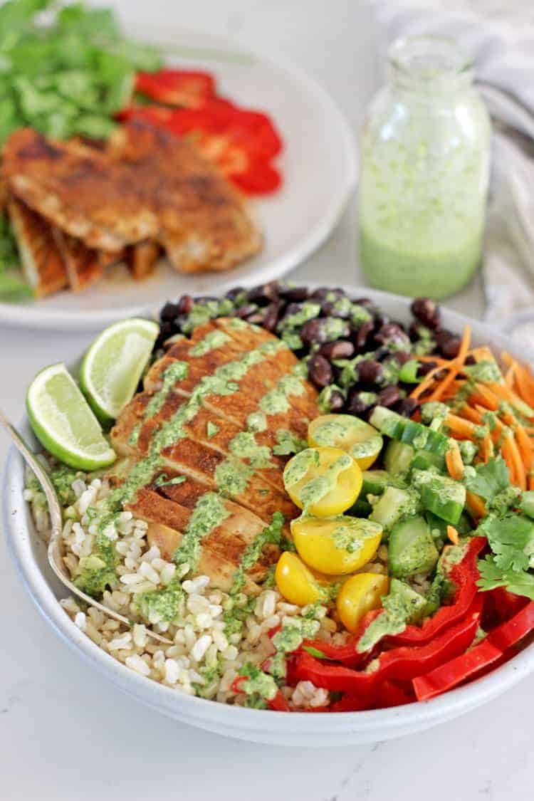 Chicken burrito bowl with a fork on a white background and salad in the background