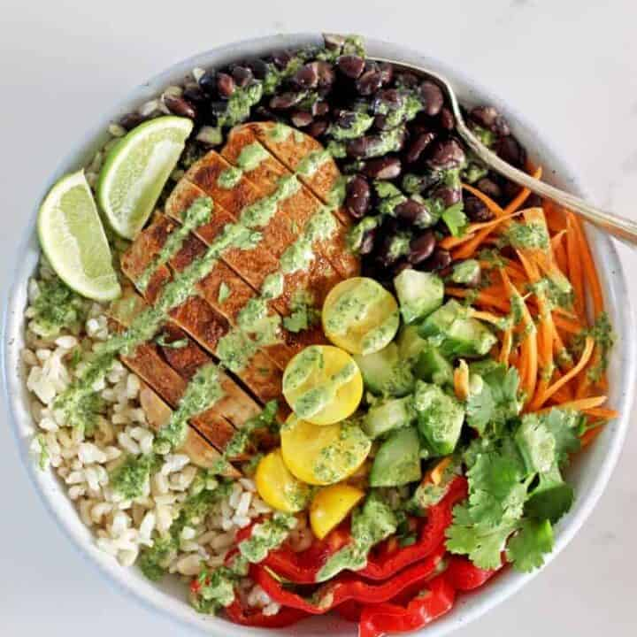 Chicken burrito bowl with a fork on a white background