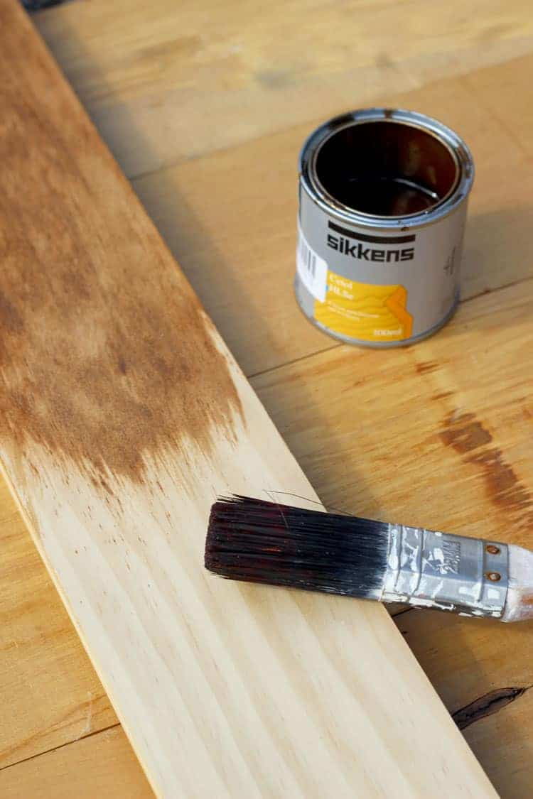 Pine board being stained with paintbrush