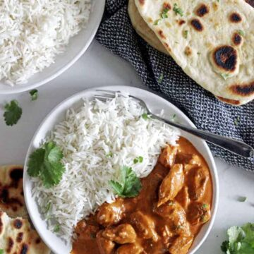 Overhead shot of white bowl with butter chicken and rice with bowl of white rice, naan bread and blue tea towel in background