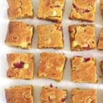 Close up of raspberry and white chocolate blondies on white background