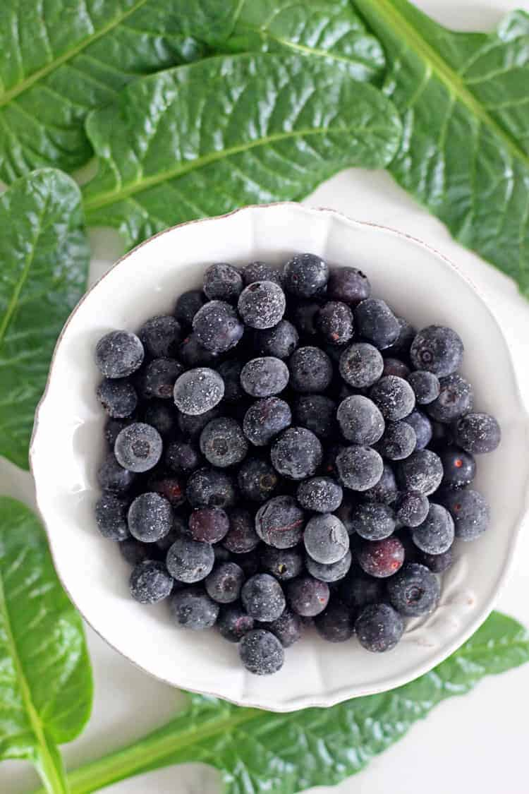 Bowl of frozen blueberries surrounded by baby spinach leaves