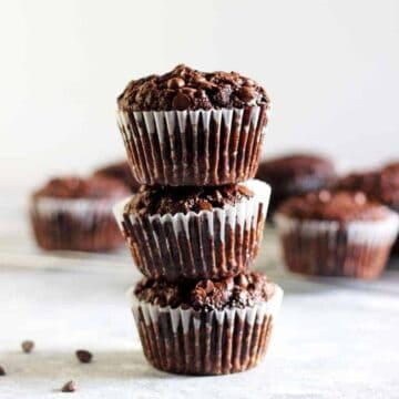 Stack of 3 double chocolate muffins with more muffins in the background