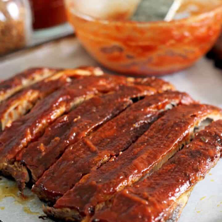 Oven baked pork ribs with bowl of BBQ sauce on an oven tray