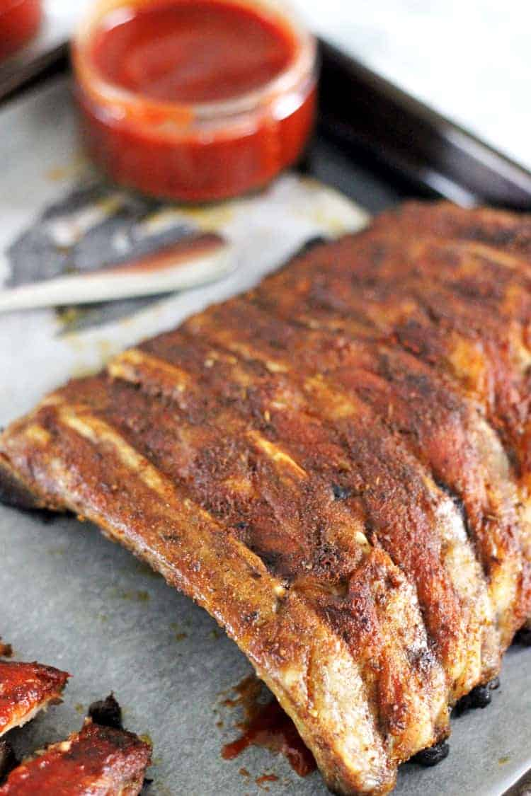 Rack of BBQ pork ribs with dry rub coating on baking tray