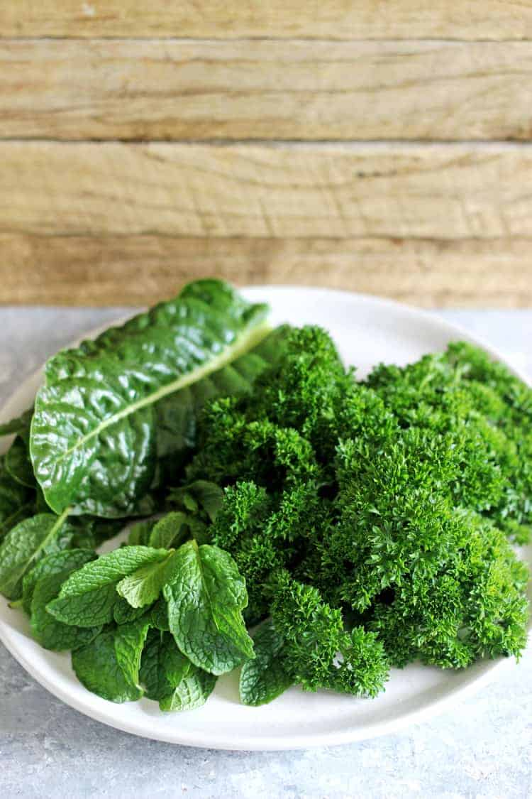 Bowl with spinach, parsley & mint leaves in front of a wooden background