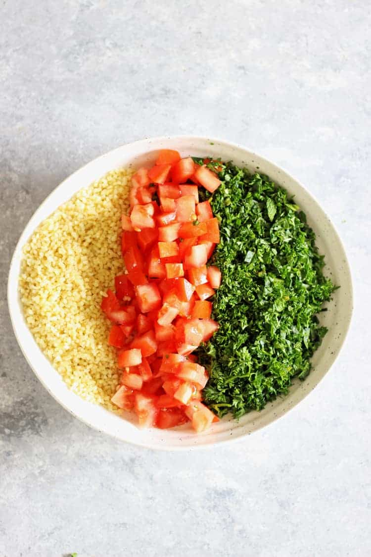 Bowl with bulgur wheat, tomatoes and fresh herbs on a white background