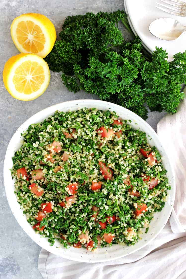 Overhead image of tabbouleh salad in a white bowl with a bunch of parsley and lemons in the background