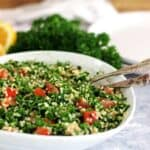 Tabbouleh Salad in a white bowl with fresh parsley and lemons in the background