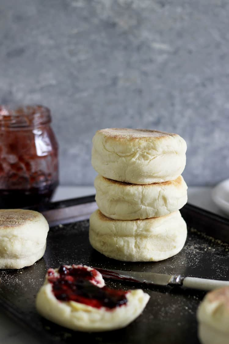 Stack of 3 English Muffins on a baking tray with knife and split muffin with jam in foreground