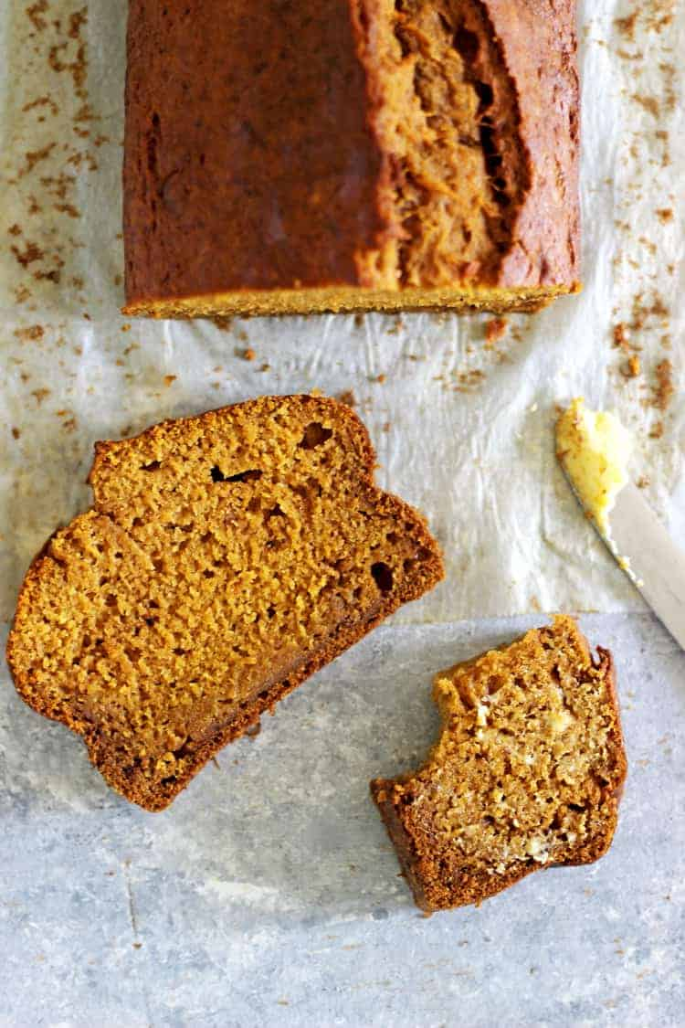 Loaf of pumpkin spice bread from overhead on a white background with 2 slices and a knife with butter