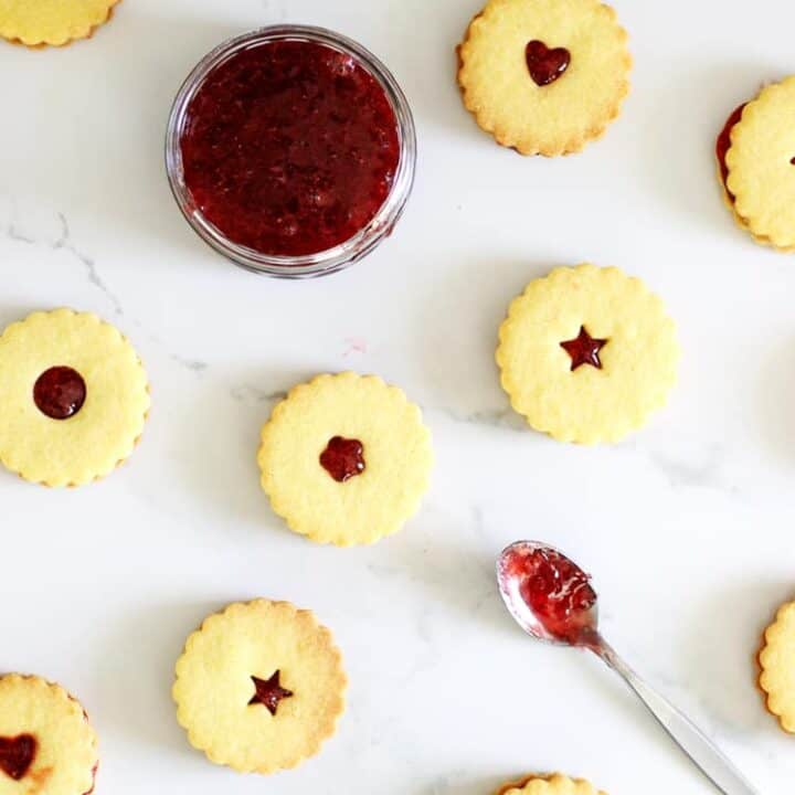 Overhead of homemade shrewsbury biscuits with homemade strawberry jam in a bowl