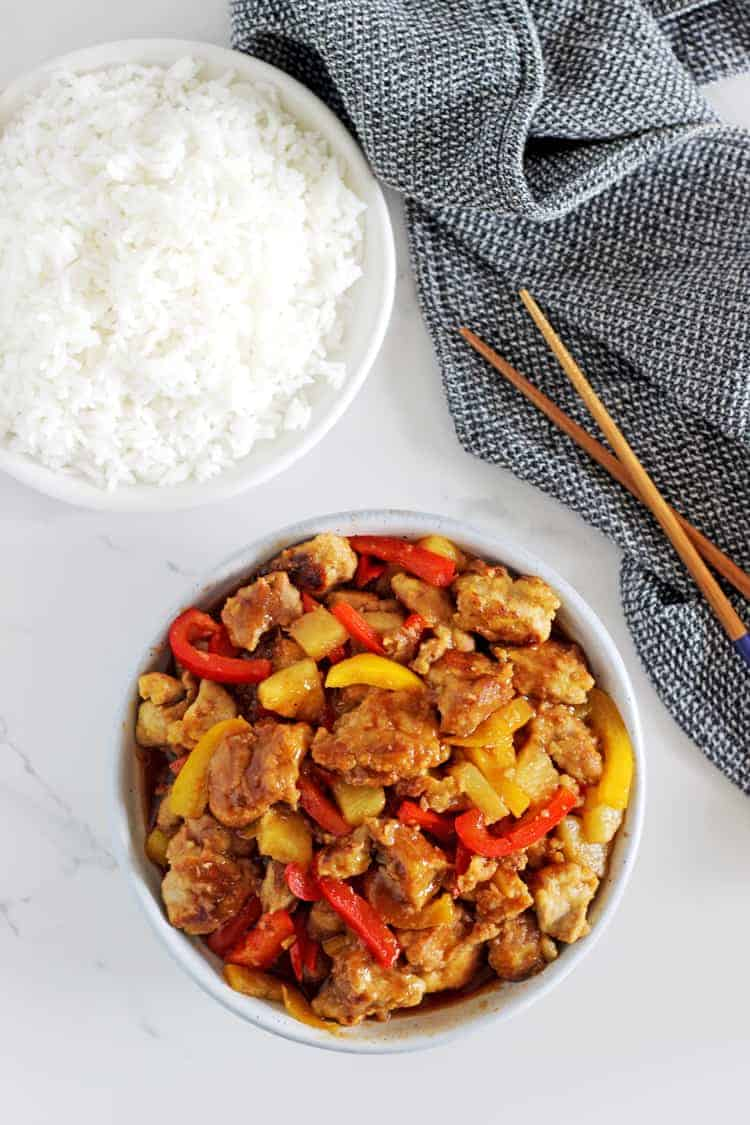 Bowl of sweet and sour pork stirfry with white rice and a tea towel and chopsticks on the table