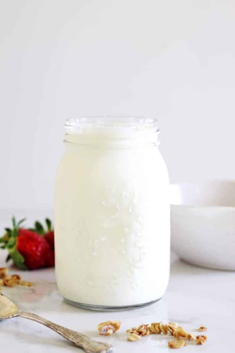 Jar of yoghurt on white background with berries
