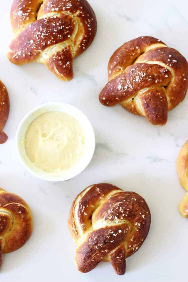 Overhead shot of soft pretzels on white background with cheese dipping sauce