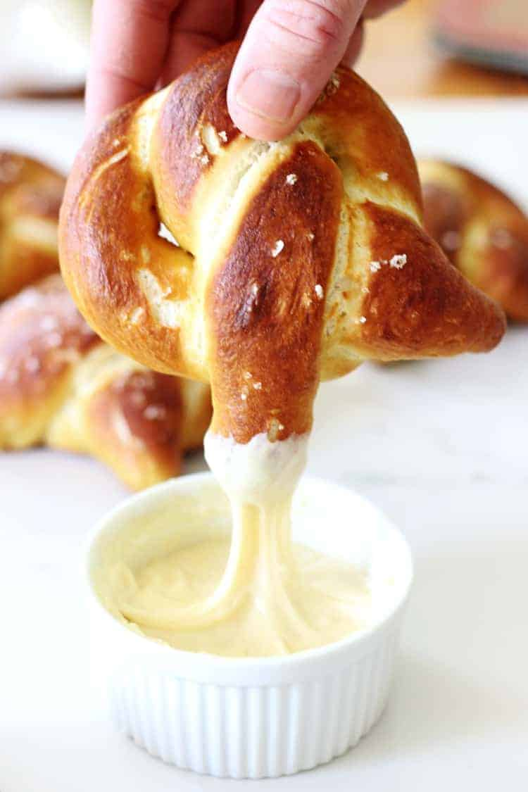 Shot of homemade soft pretzel being dipped into cheese sauce