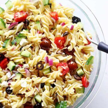 Glass bowl of Greek pasta salad on white background