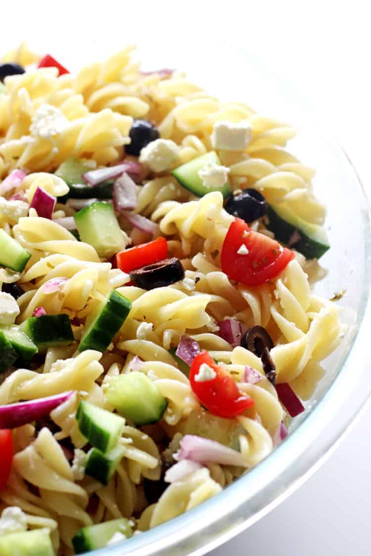 Glass bowl of Greek pasta salad on white background