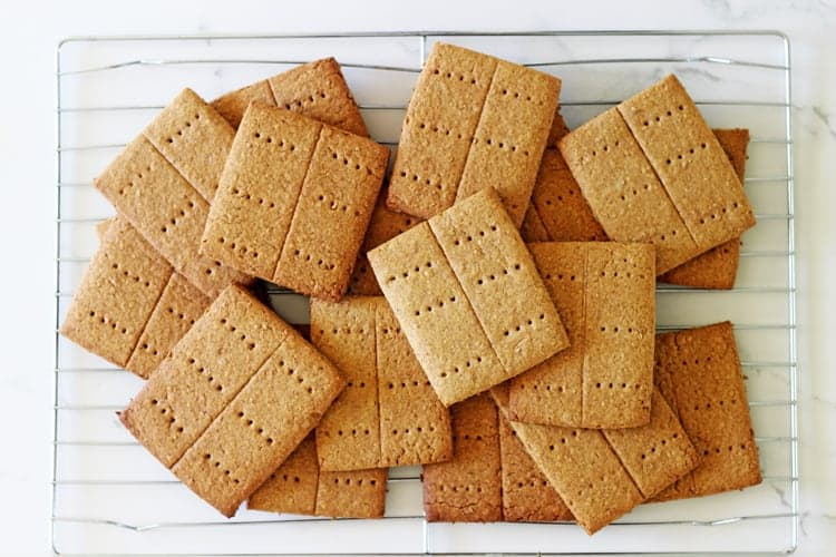 Homemade graham crackers on cooling rack on white marble background