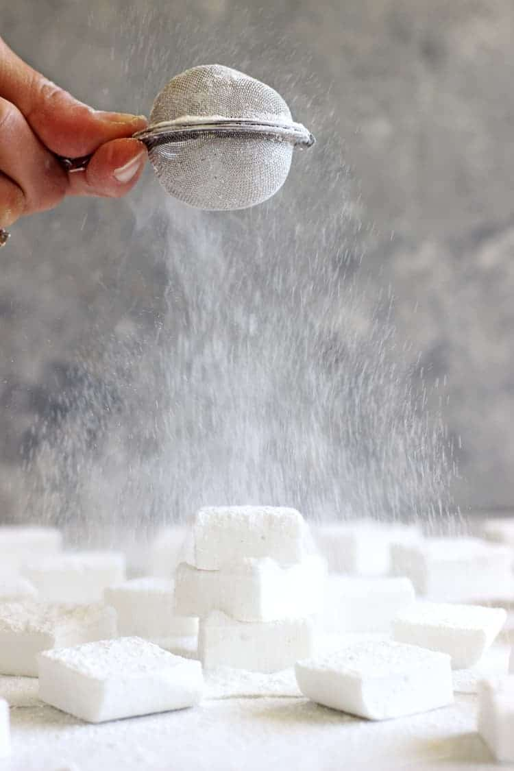Homemade marshmallows in front of a grey background with hand holding strainer sprinkling powdered sugar over a stack of marshmallows