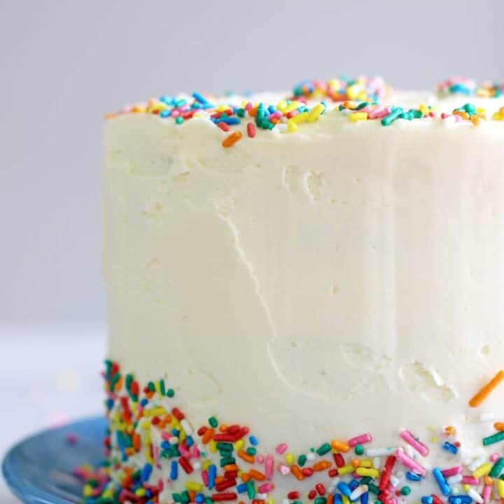 6 inch sprinkles layer cake on a blue plate with a sprinkled 30 on top