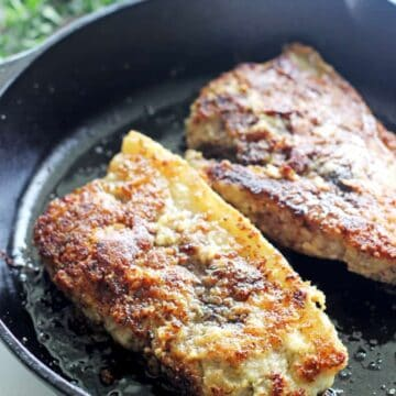 Parmesan pork chops cooking in a cast iron frying pan