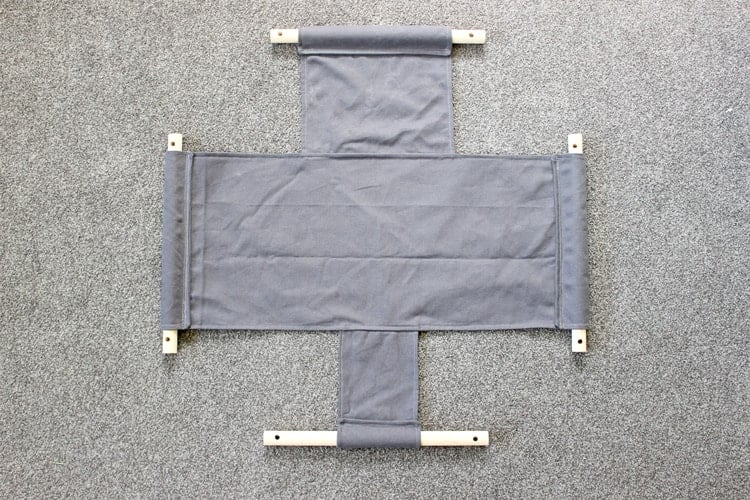 Canvas baby swing with dowel rods in place laid out on floor