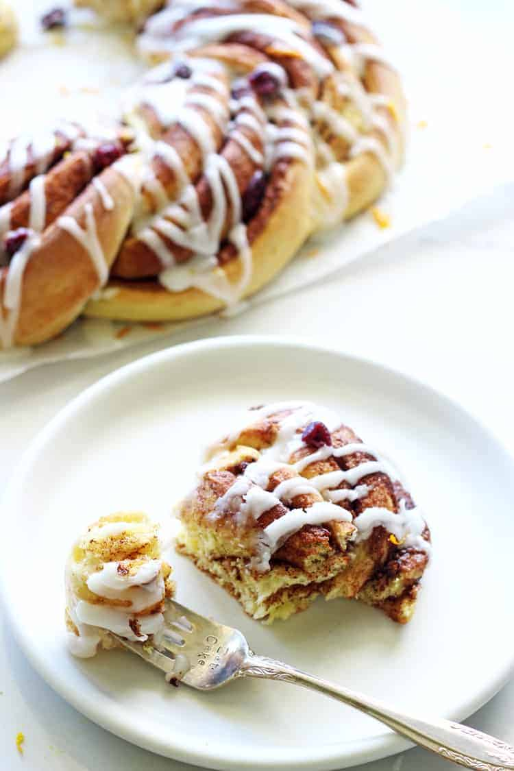 Cinnamon roll on a white plate with wreath in background
